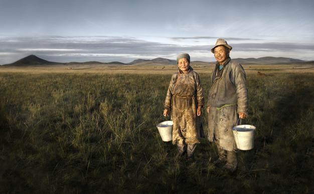 Mongolian farmers holding basin in the field
